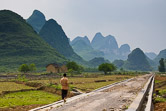Chinese boy walinkg on a newly constructed road in ricefields in Guangxi